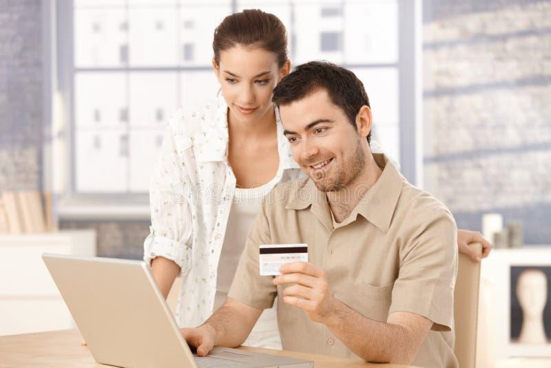 Ευτυχές ζεύγος που ψωνίζει on-line στο σπίτι χαμογελώντας στοκ εικόνες