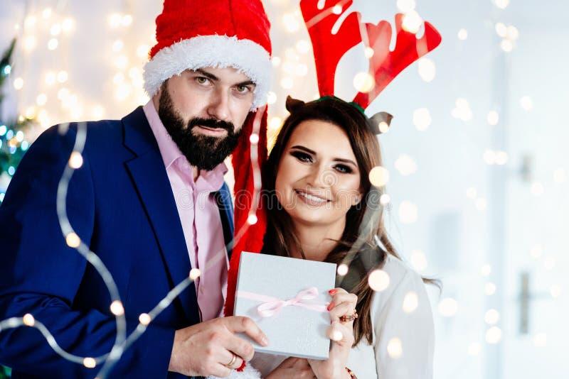Ευτυχές ζεύγος στα καπέλα Χριστουγέννων που κρατά το κιβώτιο δώρων στοκ εικόνα