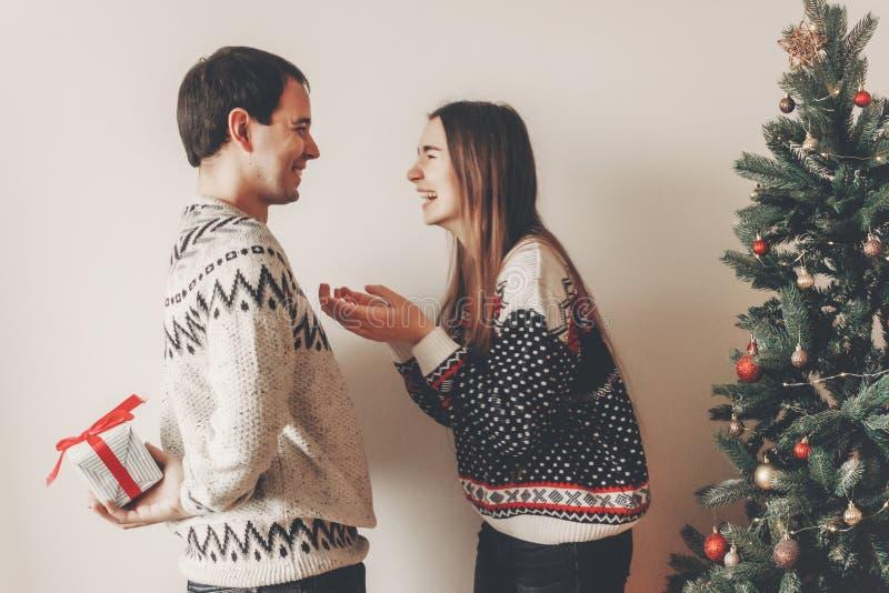 Ευτυχές ζεύγος στα μοντέρνα πουλόβερ που ανταλλάσσει τα δώρα στο εορταστικό roo στοκ εικόνα
