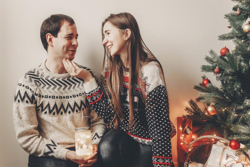 Ευτυχές ζεύγος στα μοντέρνα πουλόβερ που κρατά το φως φαναριών στο festiv στοκ εικόνες