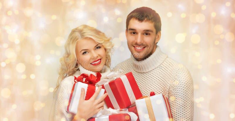 Ευτυχές ζεύγος στα πουλόβερ που κρατά τα δώρα Χριστουγέννων στοκ εικόνες με δικαίωμα ελεύθερης χρήσης