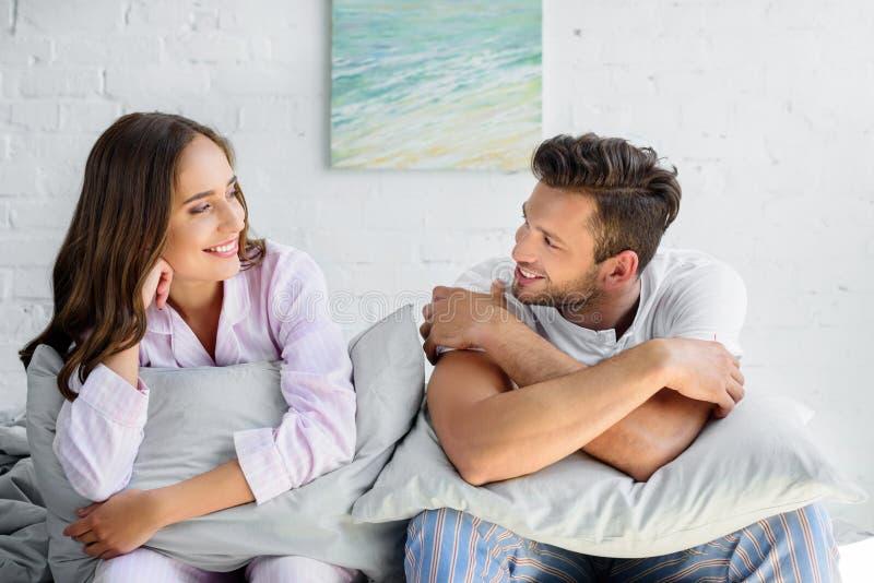 ευτυχές ζεύγος στις πυτζάμες που κάθεται στο κρεβάτι με τα μαξιλάρια και το κοίταγμα στοκ φωτογραφία