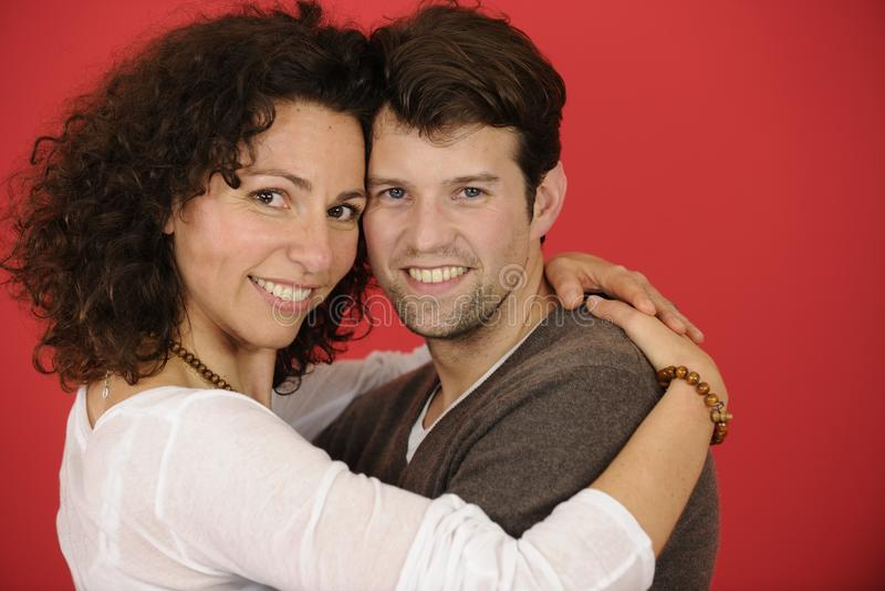 Ευτυχές ζεύγος στο κόκκινο υπόβαθρο στοκ φωτογραφία