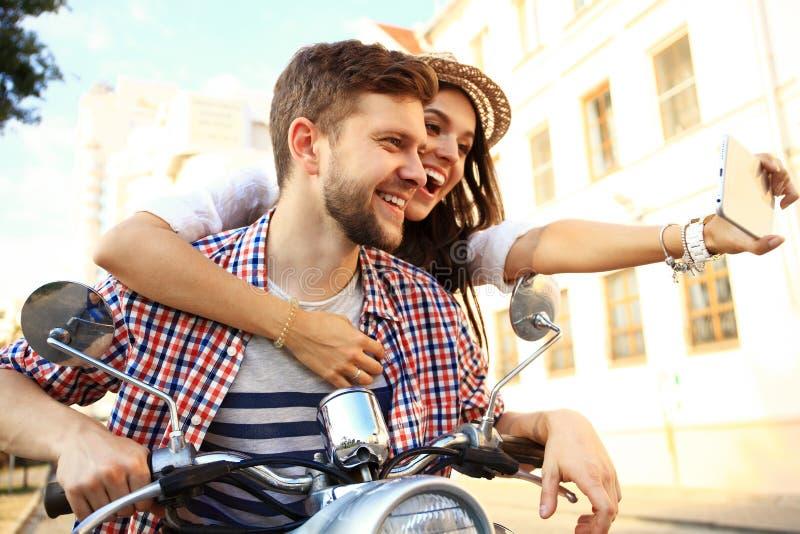 Ευτυχές ζεύγος στο μηχανικό δίκυκλο που κάνει selfie τη φωτογραφία στο smartphone στοκ φωτογραφίες με δικαίωμα ελεύθερης χρήσης