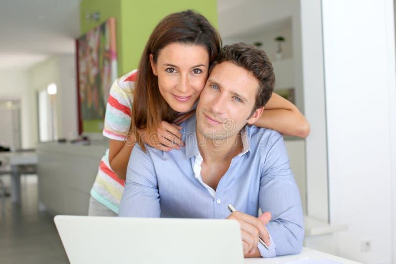 Ευτυχές ζεύγος στο σπίτι με τον υπολογιστή στοκ εικόνα με δικαίωμα ελεύθερης χρήσης