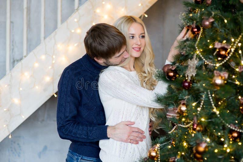 Ευτυχές ζεύγος των εραστών στα πουλόβερ που διακοσμούν το χριστουγεννιάτικο δέντρο στοκ εικόνα με δικαίωμα ελεύθερης χρήσης