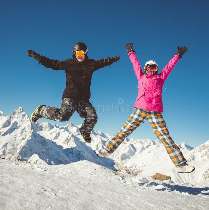Ευτυχές ζεύγος των snowboarders που πηδά στα αλπικά βουνά στοκ εικόνα