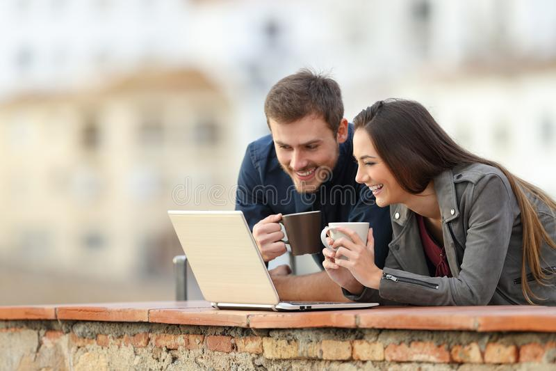 Ευτυχές ζεύγος χρησιμοποιώντας ένα lap-top και πίνοντας στις διακοπές στοκ εικόνες με δικαίωμα ελεύθερης χρήσης
