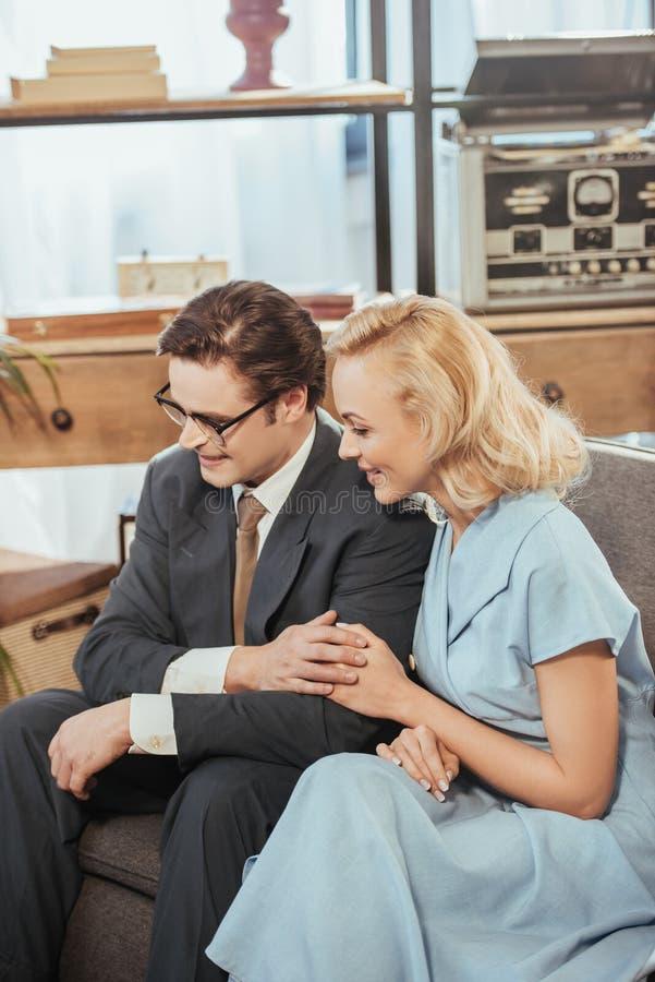 ευτυχές ζεύγος ύφους δεκαετίας του '50 που κοιτάζει μακριά καθμένος στον καναπέ στοκ εικόνα με δικαίωμα ελεύθερης χρήσης