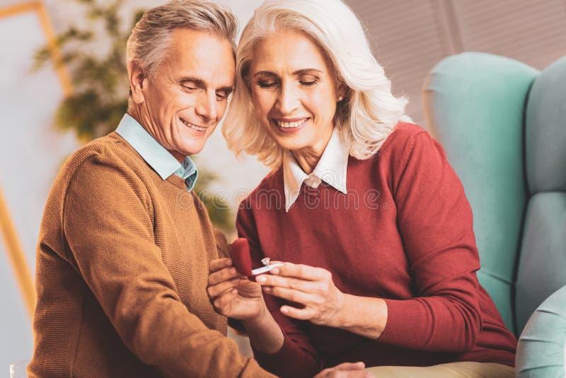 Ευτυχές ηλικιωμένο ζεύγος που εξετάζει το συμπαθητικό δαχτυλίδι στοκ φωτογραφία με δικαίωμα ελεύθερης χρήσης