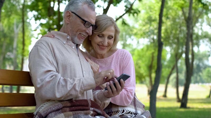 Ευτυχές ηλικιωμένο ζεύγος που καλεί τα παιδιά σε απευθείας σύνδεση, καθμένος έξω, smartphone app στοκ εικόνα