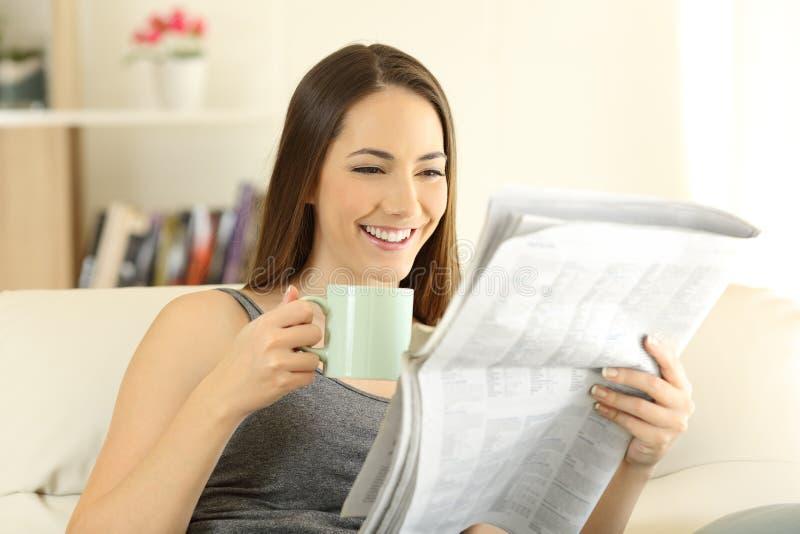 Ευτυχές θηλυκό που διαβάζει μια εφημερίδα σε έναν καναπέ στοκ φωτογραφία με δικαίωμα ελεύθερης χρήσης