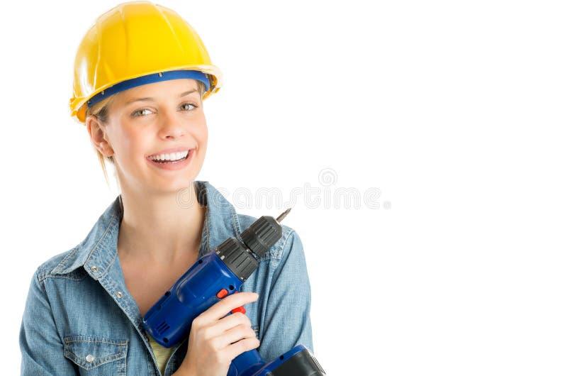 Ευτυχές θηλυκό ασύρματο τρυπάνι εκμετάλλευσης εργατών οικοδομών στοκ εικόνα με δικαίωμα ελεύθερης χρήσης
