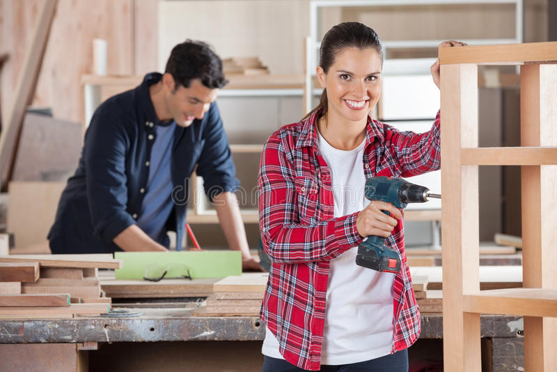 Ευτυχές θηλυκό τρυπώντας με τρυπάνι ξύλο ξυλουργών στο εργαστήριο στοκ φωτογραφία