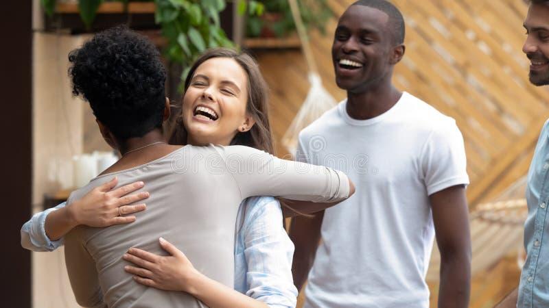 Ευτυχές καυκάσιο κορίτσι εφήβων που αγκαλιάζει τον αφρικανικό φίλο στη συνεδρίαση της ομάδας στοκ φωτογραφία με δικαίωμα ελεύθερης χρήσης