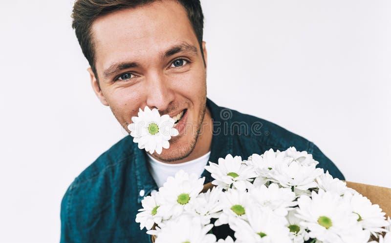 Ευτυχές καυκάσιο όμορφο άτομο που χαμογελά με ένα λουλούδι στο στόμα και την ανθοδέσμη των άσπρων λουλουδιών Ελκυστικό αρσενικό μ στοκ εικόνες