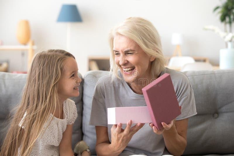 Ευτυχές κιβώτιο δώρων ανοίγματος γιαγιάδων με το παρόν από το εγγόνι στοκ φωτογραφίες με δικαίωμα ελεύθερης χρήσης