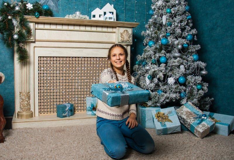 Ευτυχές κιβώτιο χριστουγεννιάτικου δώρου λαβής κοριτσιών στο πρωί διακοπών στο όμορφο εσωτερικό δωματίων Δώρο Χριστουγέννων εκμετ στοκ εικόνες