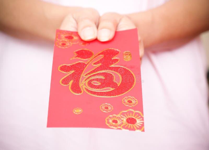 Ευτυχές κινεζικό νέο έτος, χέρι γυναικών που κρατά τον κόκκινο φάκελο στοκ φωτογραφία με δικαίωμα ελεύθερης χρήσης