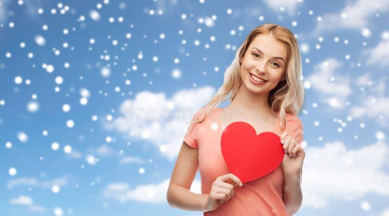 Ευτυχές κορίτσι γυναικών ή εφήβων με την κόκκινη μορφή καρδιών στοκ εικόνες