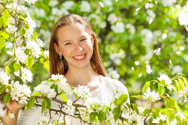 Ευτυχές κορίτσι εφήβων με τα άσπρα λουλούδια στο δέντρο στοκ εικόνες