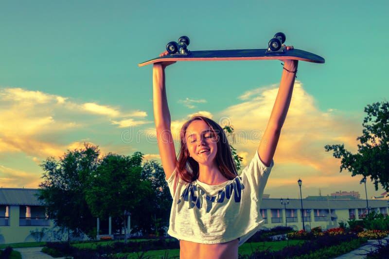 Ευτυχές κορίτσι εφήβων με skateboard της επάνω στον αέρα, τονισμένη εικόνα στοκ φωτογραφία
