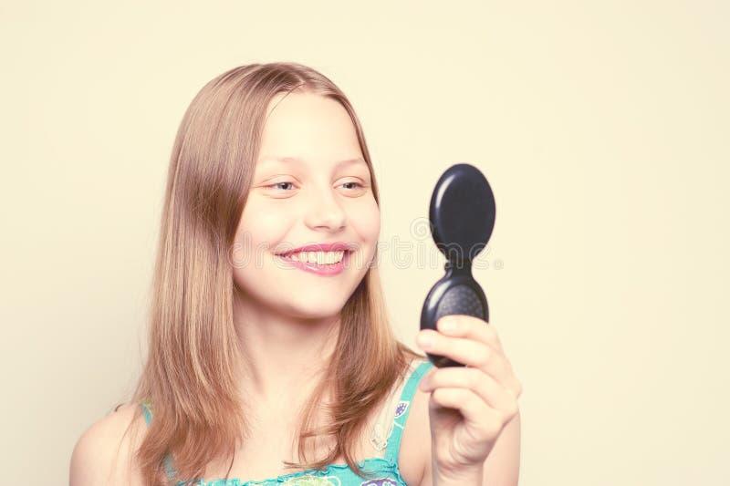 Ευτυχές κορίτσι εφήβων που εξετάζει τον καθρέφτη στοκ εικόνα με δικαίωμα ελεύθερης χρήσης