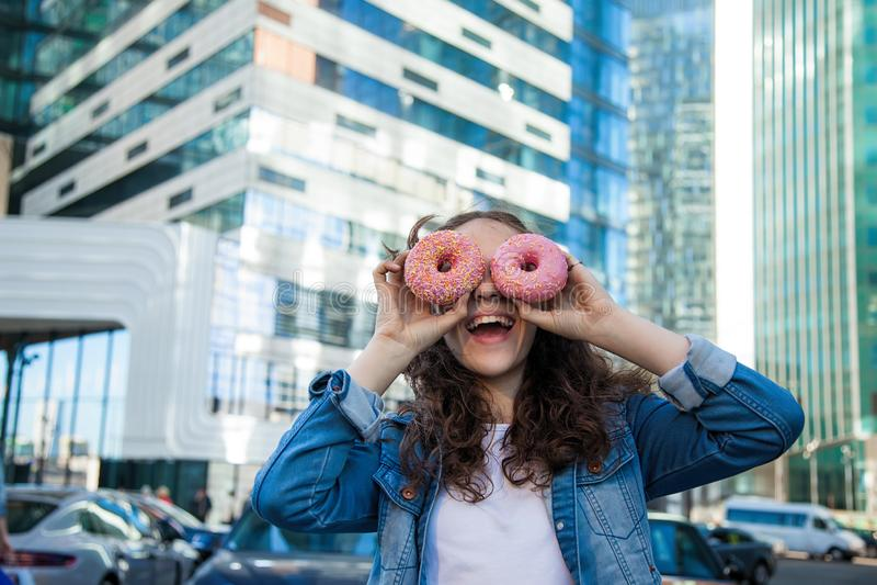 Ευτυχές κορίτσι εφήβων που κοιτάζει μέσω δύο ρόδινων φρέσκων donuts στη μεγάλη οδό πόλεων στοκ φωτογραφίες