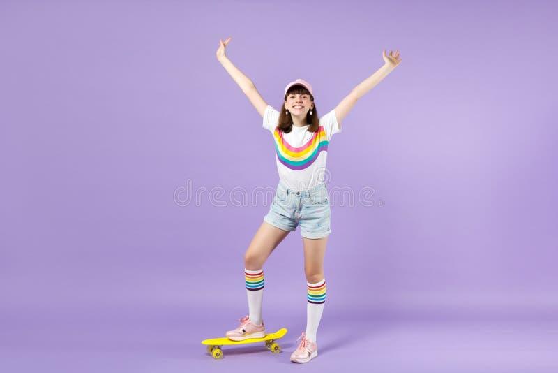 Ευτυχές κορίτσι εφήβων στα ζωηρά ενδύματα που στέκονται με κίτρινο skateboard, χέρια διάδοσης αύξησης που απομονώνονται στην ιώδη στοκ εικόνα με δικαίωμα ελεύθερης χρήσης