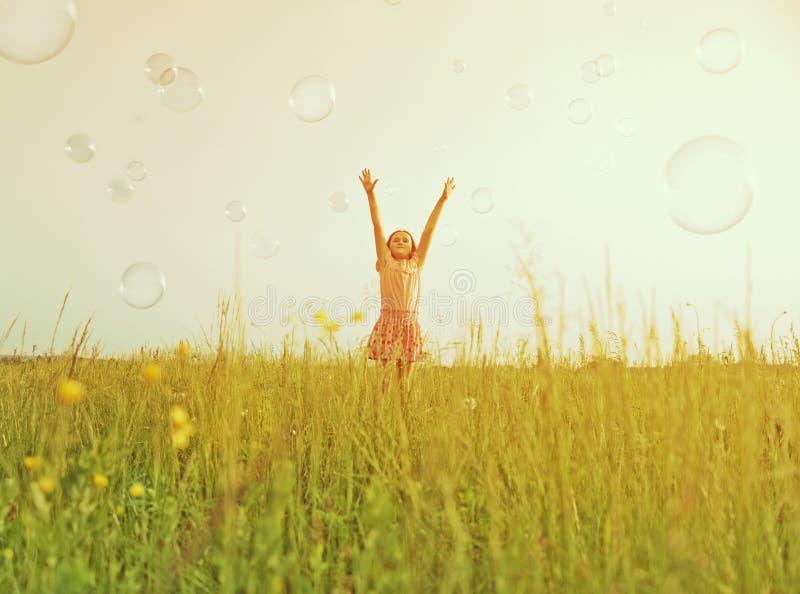 Ευτυχές κορίτσι μεταξύ των φυσαλίδων σαπουνιών στοκ εικόνες