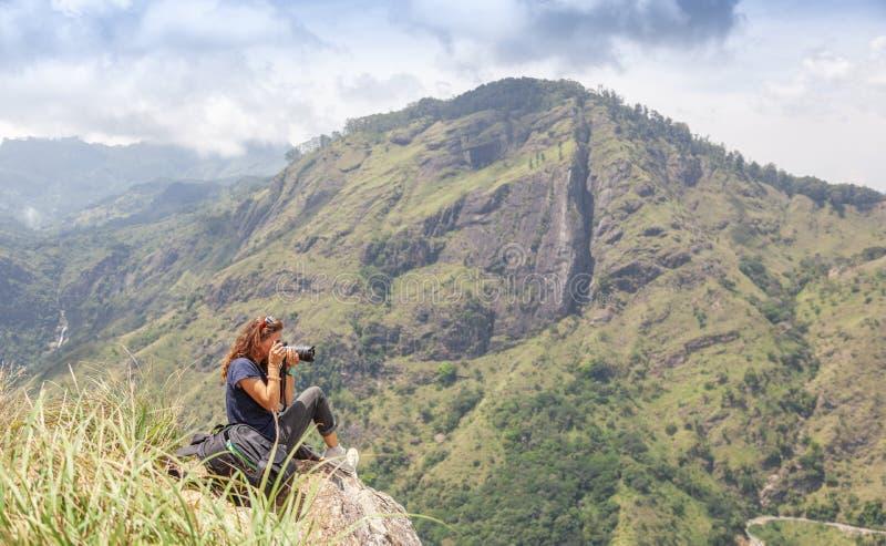 Ευτυχές κορίτσι με έναν φωτογράφο τουριστών σακιδίων πλάτης για να πάρει τις εικόνες στη κάμερα στα βουνά και να απολαύσει τη θέα στοκ φωτογραφίες με δικαίωμα ελεύθερης χρήσης