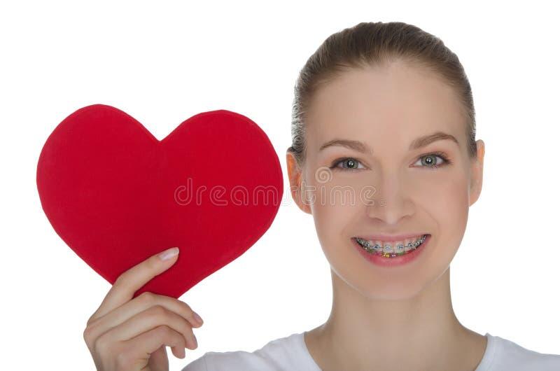 Ευτυχές κορίτσι με τα στηρίγματα στα δόντια και την κόκκινη καρδιά στοκ φωτογραφία