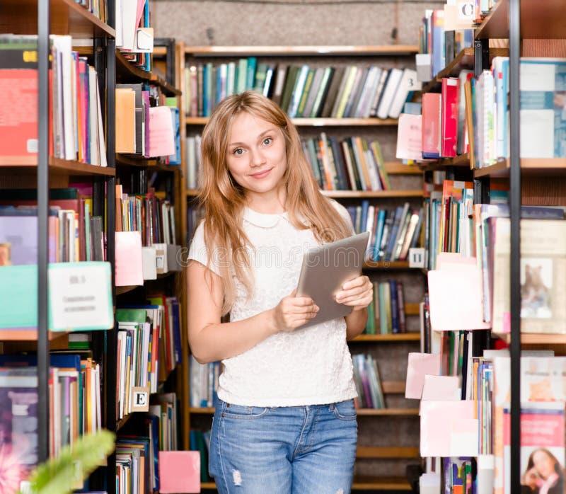 Ευτυχές κορίτσι με τον υπολογιστή ταμπλετών στη βιβλιοθήκη στοκ εικόνα