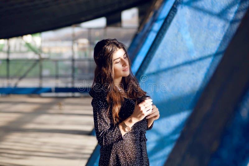 Ευτυχές κορίτσι με το μακρυμάλλη καφέ σκέψης και κατανάλωσης μέσα στη δομή πόλεων grunge Νέα γυναίκα με το μίας χρήσης φλυτζάνι στοκ εικόνα με δικαίωμα ελεύθερης χρήσης
