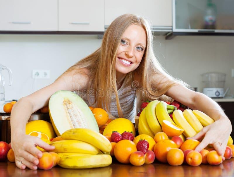 Ευτυχές κορίτσι με το σωρό των διάφορων φρούτων στοκ φωτογραφίες