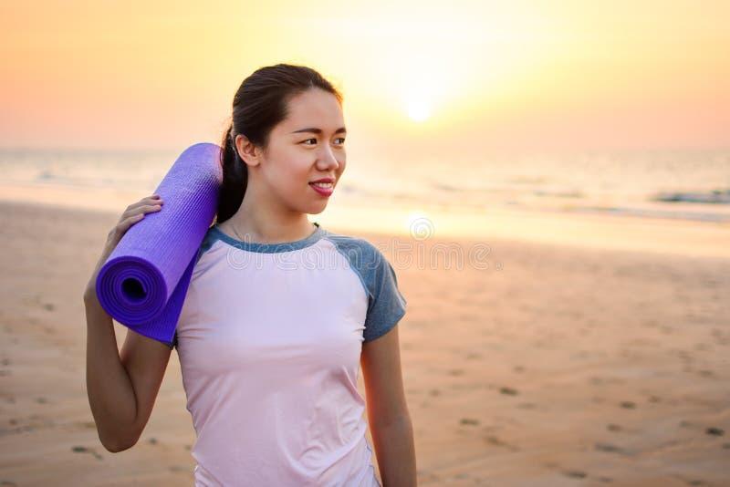 Ευτυχές κορίτσι με το χαλί γιόγκας στην παραλία στοκ εικόνα με δικαίωμα ελεύθερης χρήσης