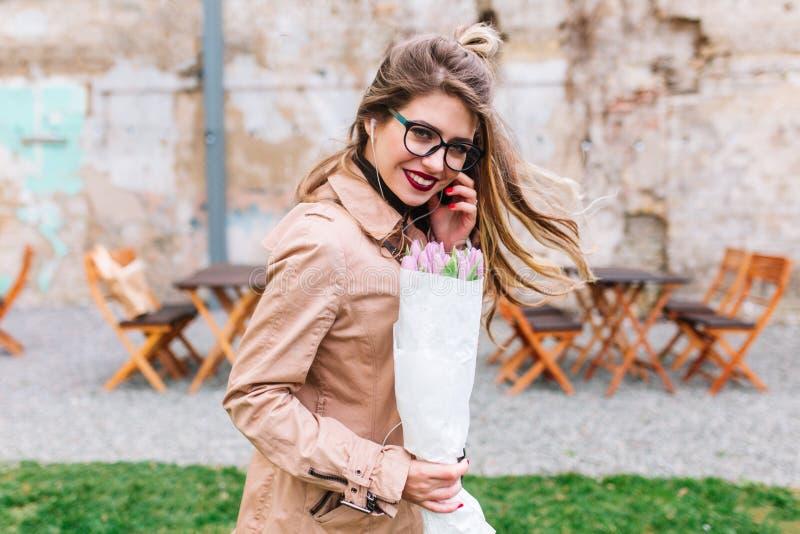 Ευτυχές κορίτσι με το χαριτωμένο hairstyle που θέτει πρόθυμα με την τρίχα που κυματίζει στον αέρα και που γελά κατά την ημερομηνί στοκ φωτογραφία με δικαίωμα ελεύθερης χρήσης