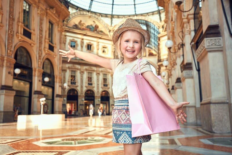 Ευτυχές κορίτσι μόδας με τη ρόδινη τσάντα αγορών να χαρεί Galleria στοκ εικόνες