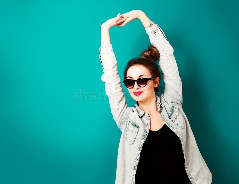 Ευτυχές κορίτσι μόδας Hipster στο τυρκουάζ υπόβαθρο στοκ εικόνα