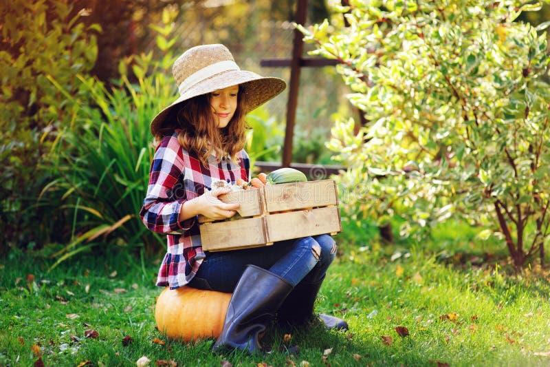 Ευτυχές κορίτσι παιδιών αγροτών με τη συγκομιδή φθινοπώρου - οργανικά κολοκύθες, καρότα και κολοκύθια που επιλέγονται από τον κήπ στοκ φωτογραφία