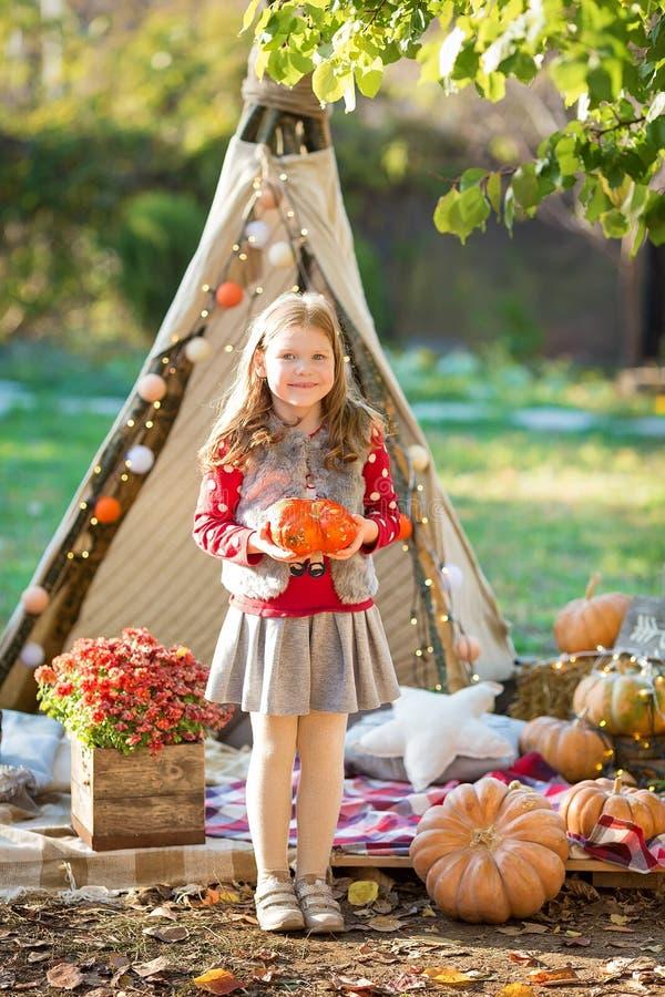 Ευτυχές κορίτσι παιδιών με την κολοκύθα υπαίθρια στο πάρκο αποκριών στοκ εικόνα με δικαίωμα ελεύθερης χρήσης