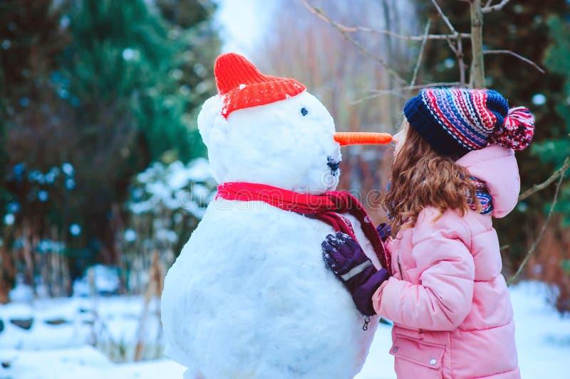 ευτυχές κορίτσι παιδιών που έχει τη διασκέδαση και που στηρίζεται το χιονάνθρωπο στο χειμερινό περίπατο στο χιονώδη κήπο στοκ φωτογραφίες