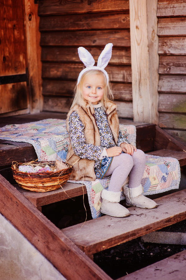 Ευτυχές κορίτσι παιδιών που φορά τα αυτιά λαγουδάκι για τη συνεδρίαση Πάσχας στη σκάλα εξοχικών σπιτιών στοκ φωτογραφία με δικαίωμα ελεύθερης χρήσης