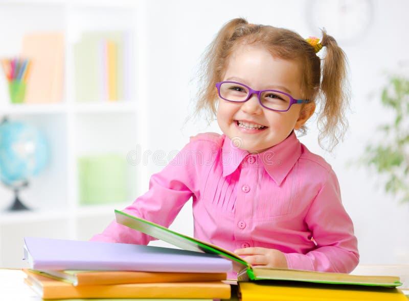 Ευτυχές κορίτσι παιδιών στα γυαλιά που διαβάζει τα βιβλία στο δωμάτιο στοκ εικόνα με δικαίωμα ελεύθερης χρήσης