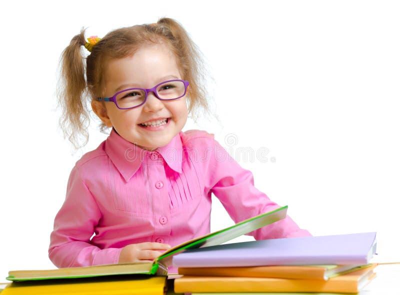 Ευτυχές κορίτσι παιδιών στα γυαλιά που διαβάζει το κάθισμα βιβλίων στοκ φωτογραφία με δικαίωμα ελεύθερης χρήσης