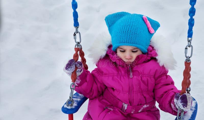 Ευτυχές κορίτσι παιδιών στην ταλάντευση το χειμώνα ηλιοβασιλέματος Παιχνίδι παιδάκι σε έναν χειμερινό περίπατο στη φύση στοκ φωτογραφίες