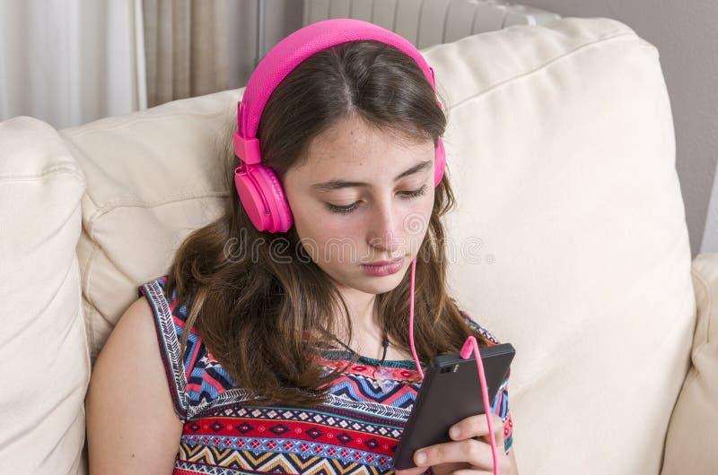 Ευτυχές κορίτσι που ακούει τη μουσική από την κινητή τηλεφωνική συνεδρίαση σε ένα cou στοκ φωτογραφίες
