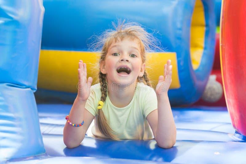 Ευτυχές κορίτσι που βρίσκεται στο μεγάλο διογκώσιμο παιχνίδι τραμπολίνων στοκ φωτογραφία με δικαίωμα ελεύθερης χρήσης