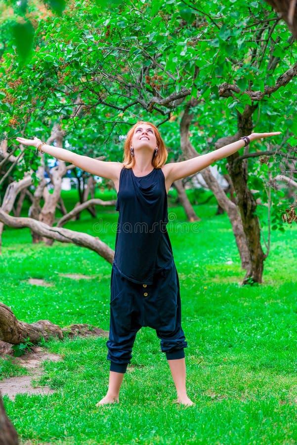 Ευτυχές κορίτσι που κάνει τη γιόγκα στο πάρκο στοκ εικόνα με δικαίωμα ελεύθερης χρήσης