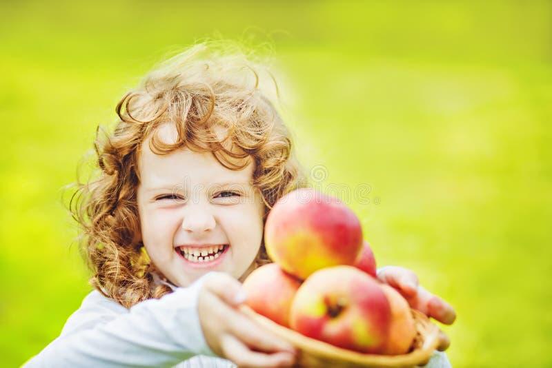Ευτυχές κορίτσι που κρατά ένα καλάθι των μήλων στο πράσινο bokeh στοκ εικόνα